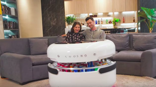 two people in front of white high-tech coffee table with opening