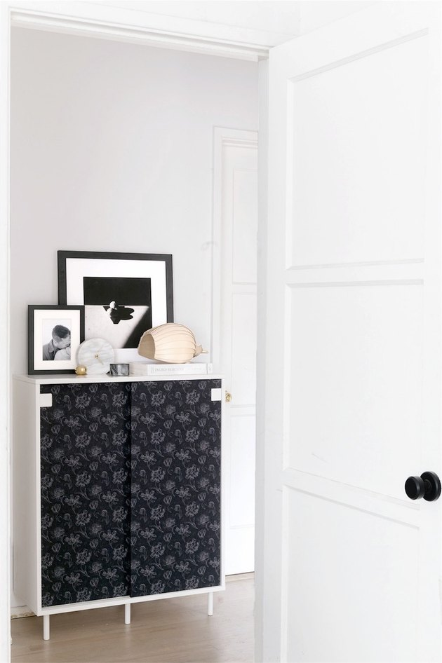 A black-wallpapered storage cabinet