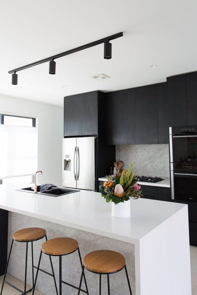 track style kitchen ceiling lights over island with black cabinets and