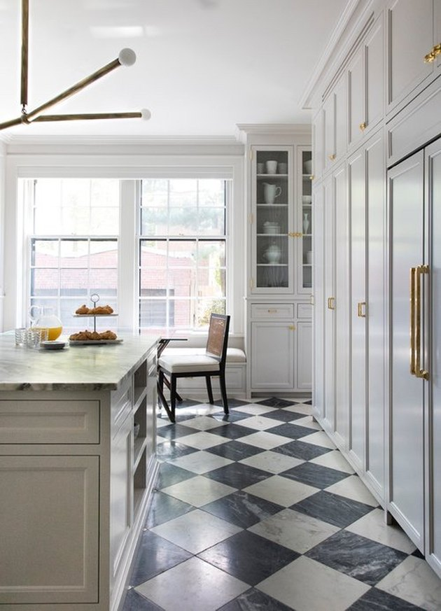 Black and white marble kitchen floor tile in harlequin pattern in a transitional kitchen designed with white cabinets and brass hardware