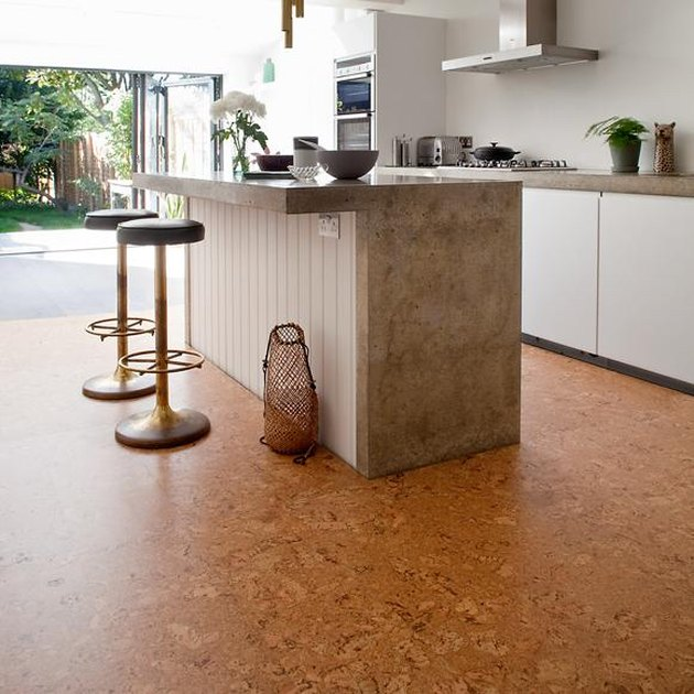 cork kitchen floor tile with white cabinets and concrete countertops