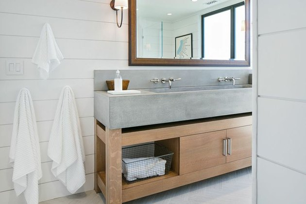 Concrete trough sink in rustic bathroom with shiplap walls