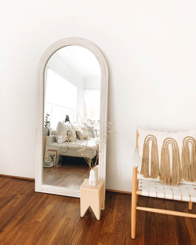 mirror, side table, chair, and pillow with tassels