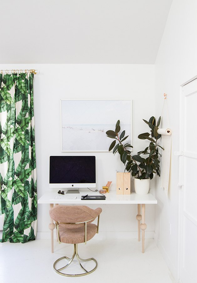 small home office with to-do list on display with paper on the wall and tropical drapery