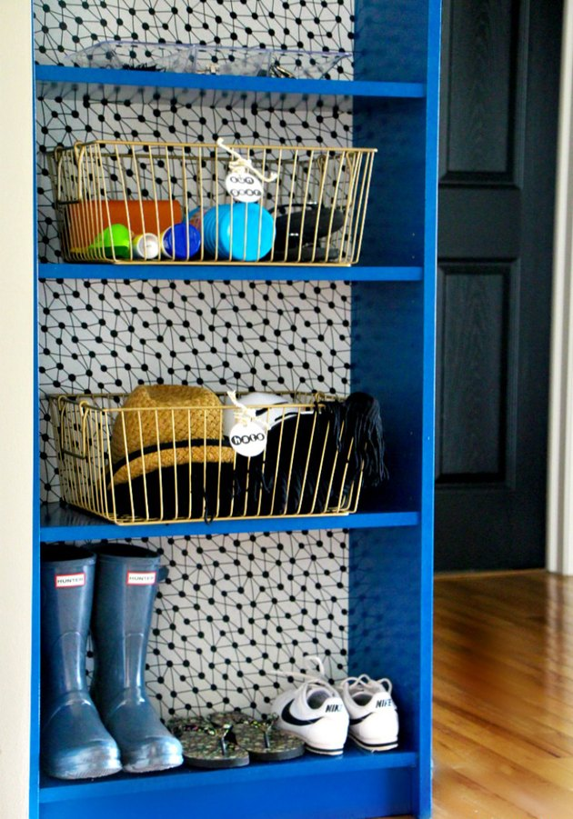 Blue bookcase with polka dot wallpaper lining the back