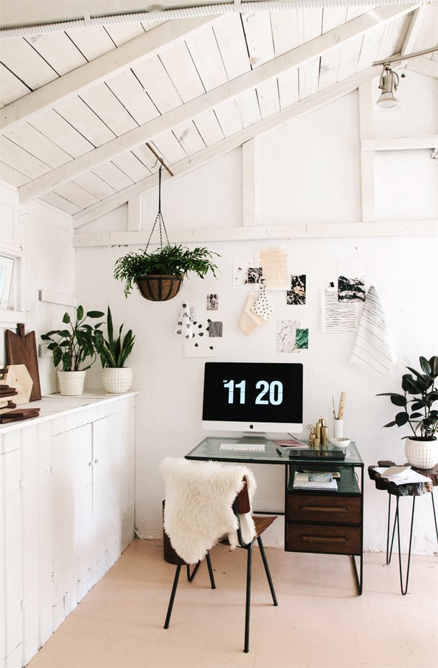 small home office with inspiration as wall art and potted plants