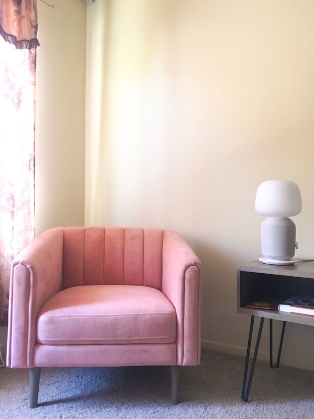 pink chair near lamp and tv stand