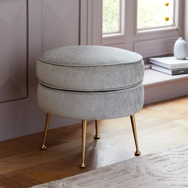 upholstered accent stool with brass legs