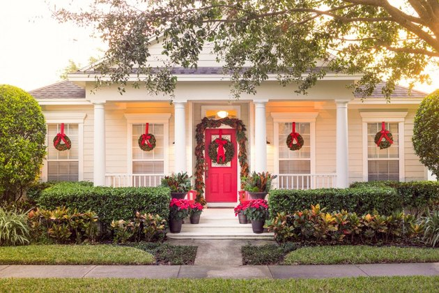 Traditional Christmas yard decorations with wreaths and red door
