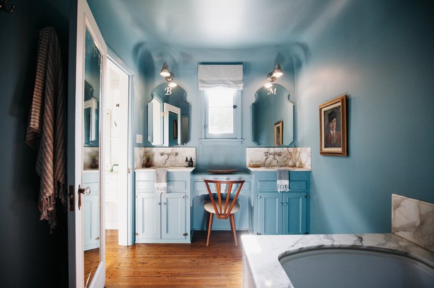 Blue wall and vanity in bathroom with marble tub
