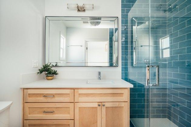bathroom with teal subway shower tile, glass shower door, light wood bathroom vanity, rectangular mirror with overhead lighting