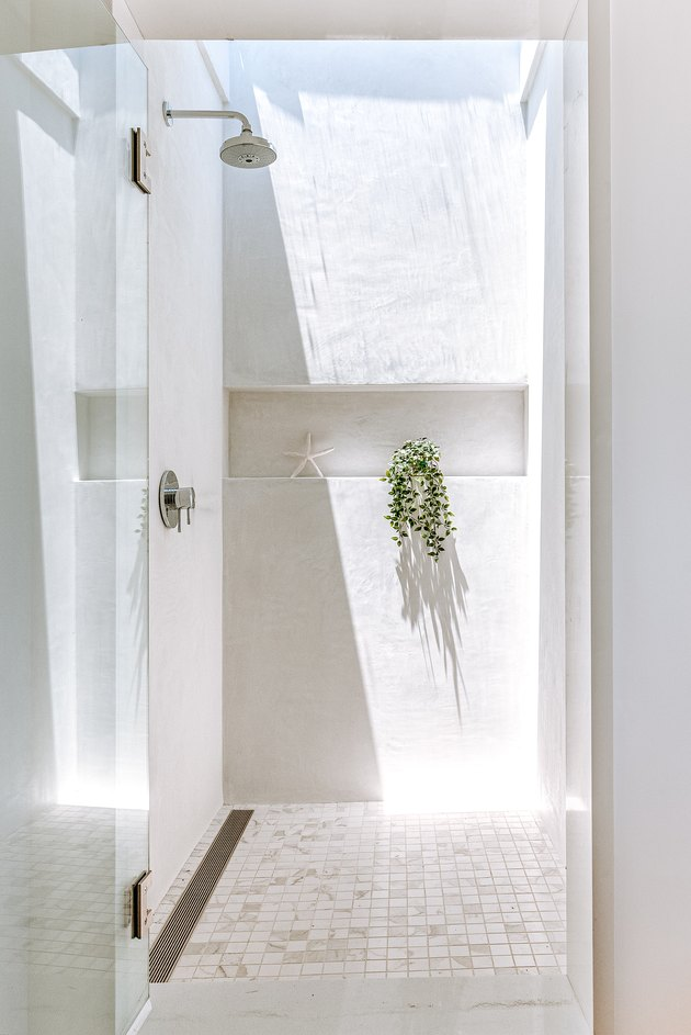 Shower with window on ceiling letting in natural light.