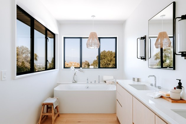 White and wood bathroom with natural pendant light over white bathtub.