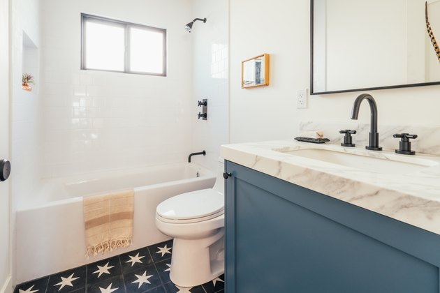 Bathroom with blue and white star tile floor and marble countertop on blue painted sink