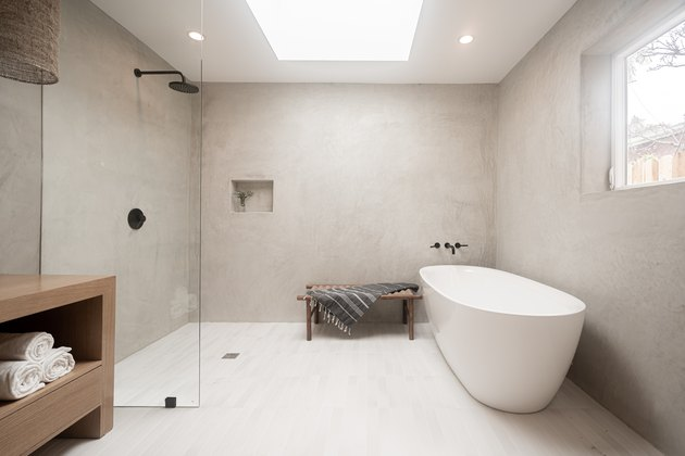 Modern bathroom with glass open shower and white bathtub