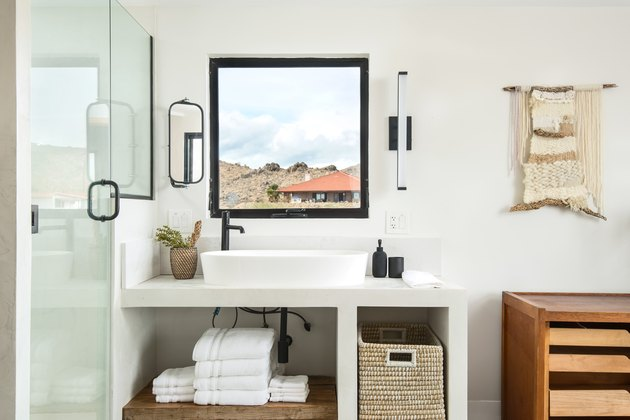 Desert-style bathroom with square window over sink and yarn wall hanging.