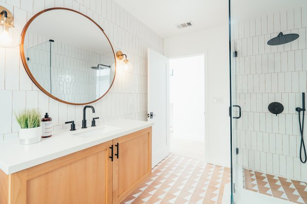Subway tiled bathroom wall, geometric tiled floor with black hardware and round mirror