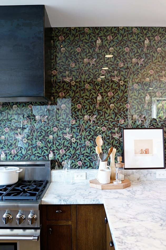 floral wallpaper kitchen backsplash with stainless steel appliances and marble countertop