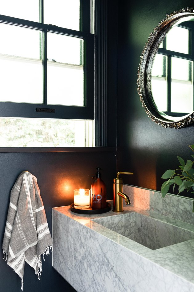 Marble sink in bathroom with dark blue painted walls and brass faucet