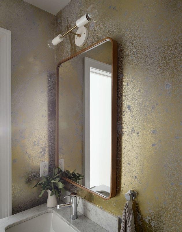Gold wallpaper on bathroom wall