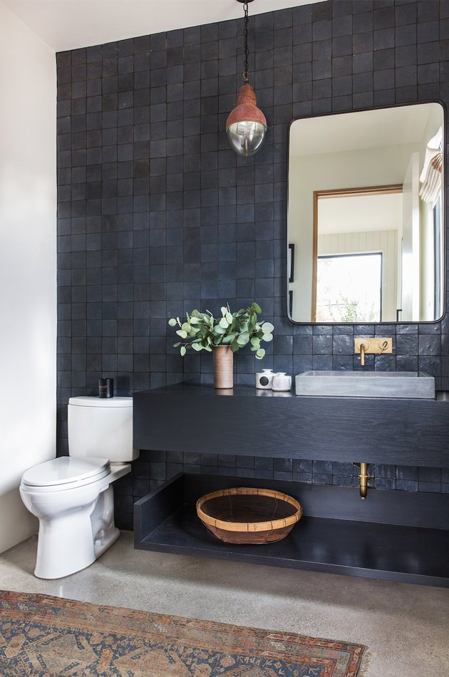 vessel bathroom sink on floating wood vanity with black wall tile