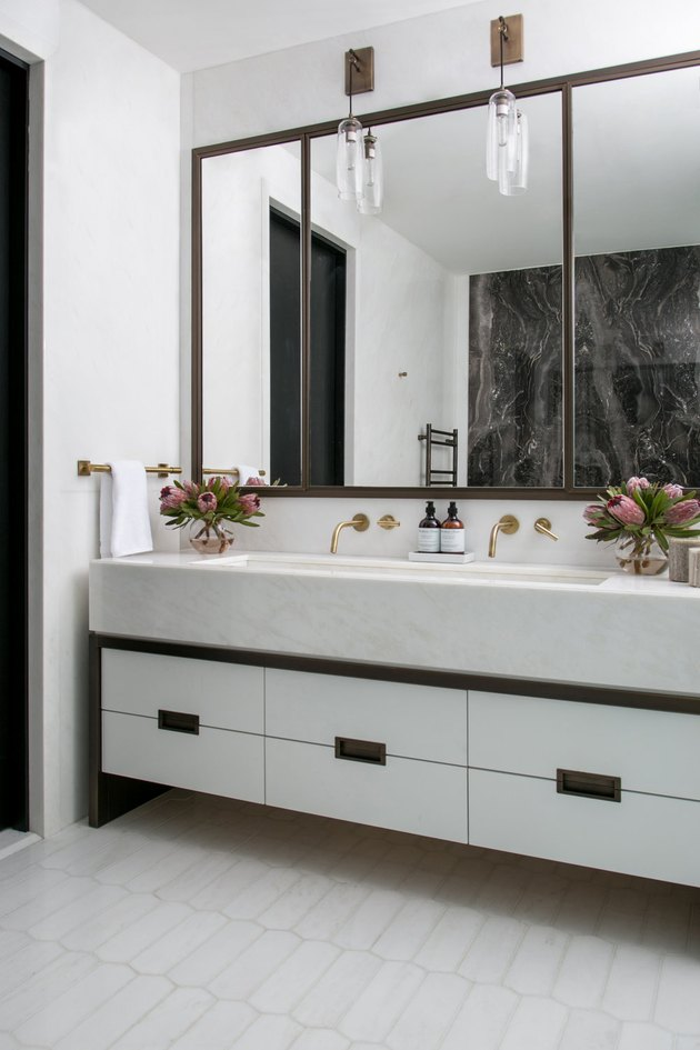 floating vanity with rectangular undermount bathroom sink and pair of brass wall-mounted faucets