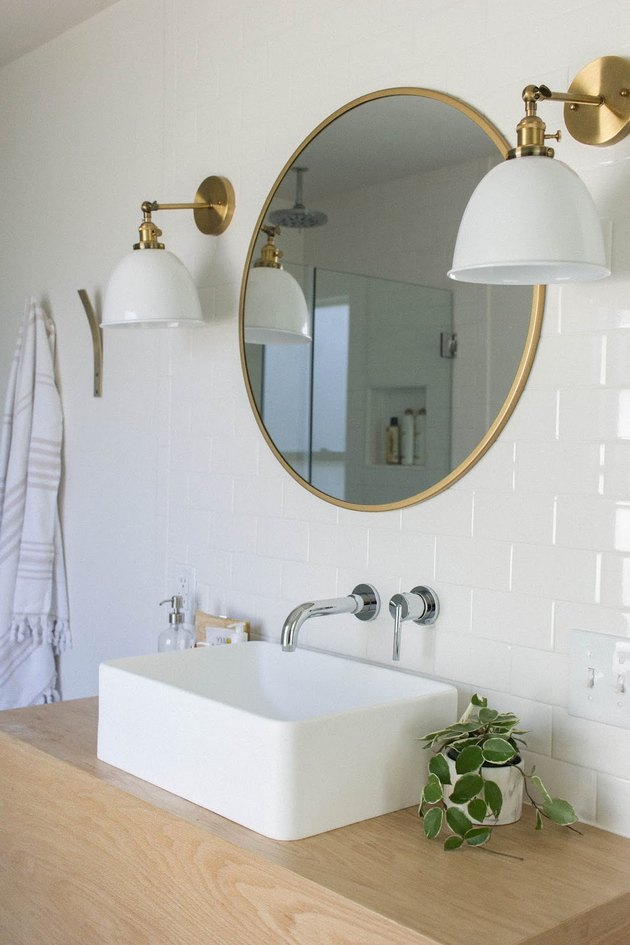 vessel bathroom sink on wood countertop with white subway wall tile