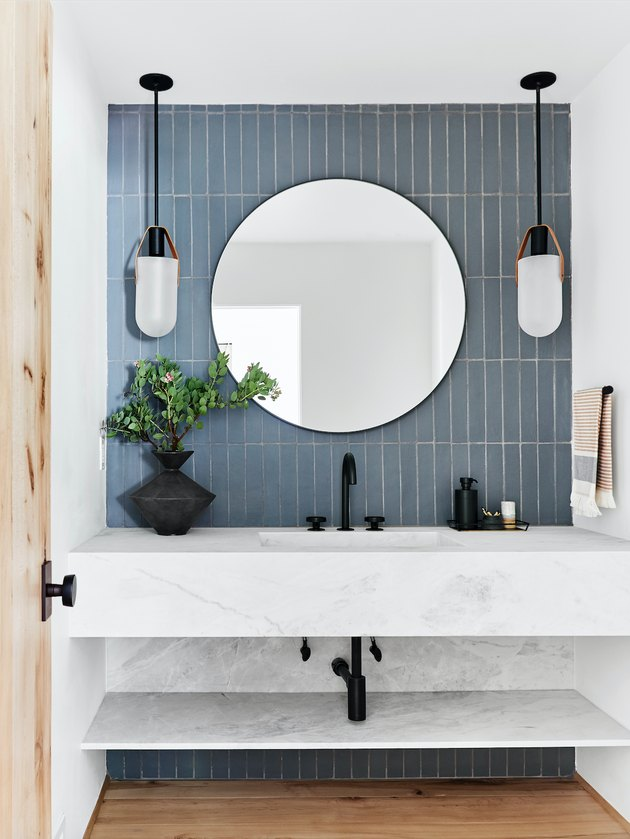 undermount bathroom sink with blue tile accent wall and pair of pendants framing round mirror