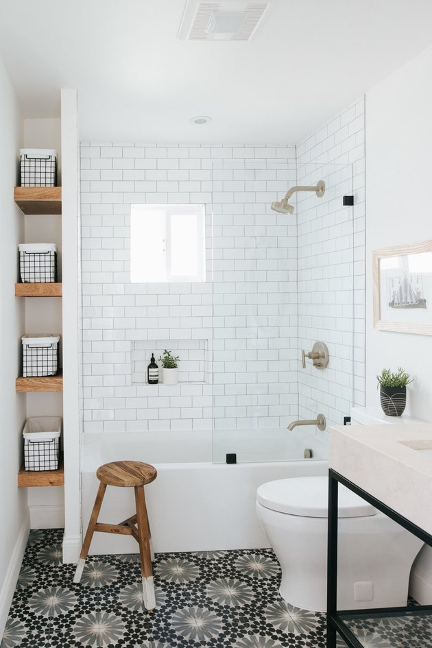 monochrome bathroom with small bathtub and storage
