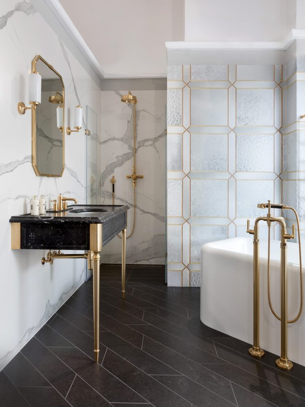 glamorous bathroom with small bathtub in the corner and console sink