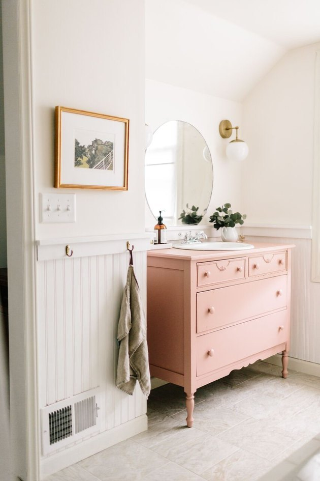 pink vintage dresser and self-rimming bathroom sink with round mirror and wall sconces