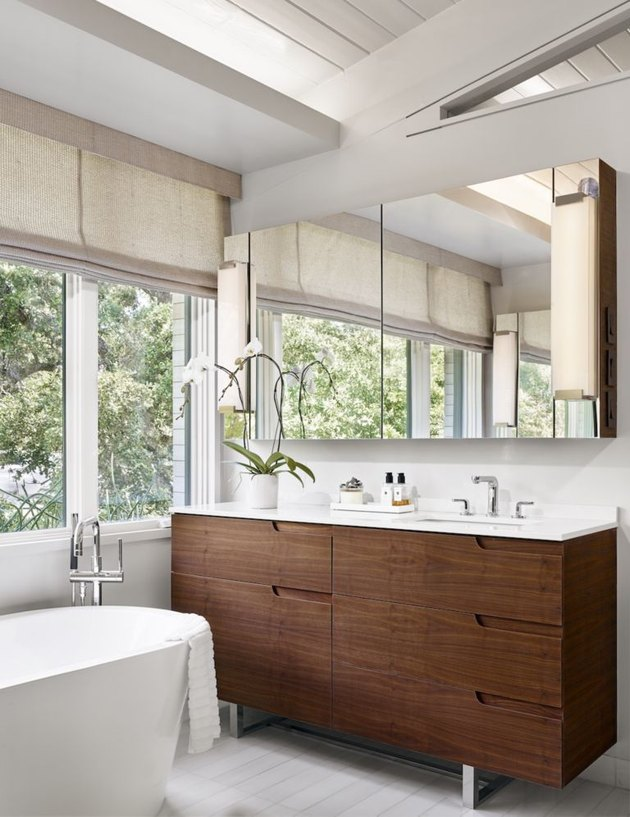 solid surface bathroom countertop with wood vanity and freestanding tub