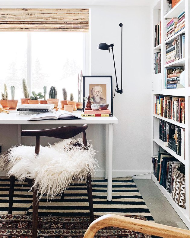 small home office with adjustable wall sconce and floor-to-ceiling bookcase