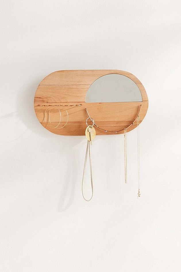 Small wooden oval wall-mounted jewelry organizer with small mirror and hooks for jewelry