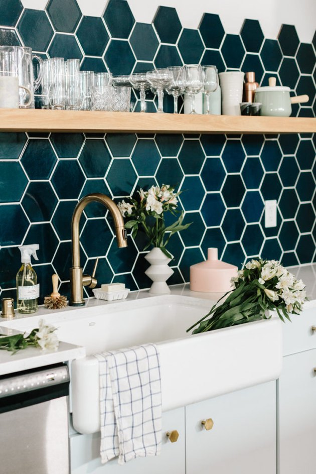 navy hexagon tile backsplash in modern kitchen with open shelving and farmhouse sink