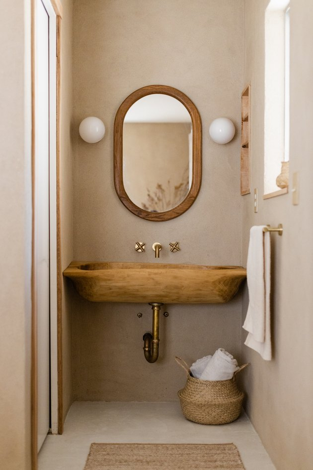 Bathroom with wood sink with natural elements, wood framed mirror and white sconces