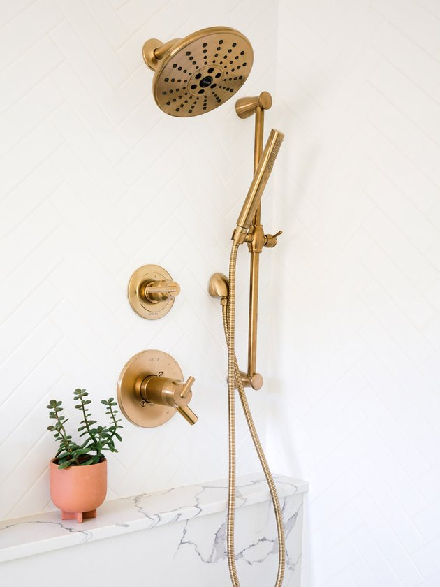brass bathroom fittings against white walls with marble