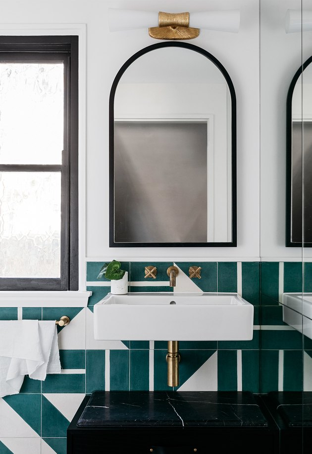 modern bathroom lighting with arched mirror above wall-mounted sink with green wall tile