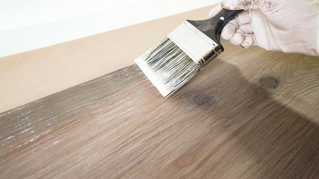 Nakładanie wybielacza na sztuczne wyblakłe wykończenie drewna.
