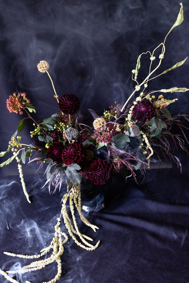 ornate flower arrangement with dark-colored flowers and smoke in background