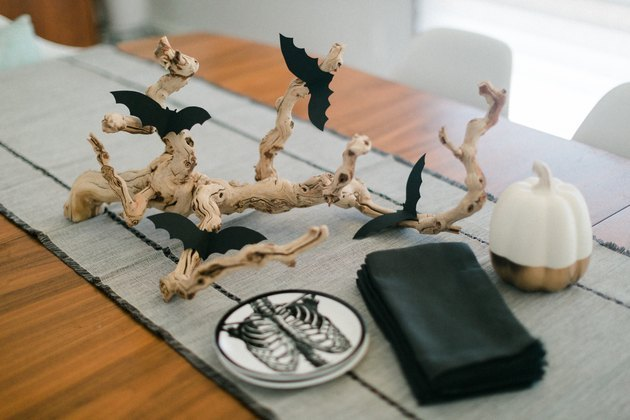 DIY branch centerpiece with bat cutouts on a table
