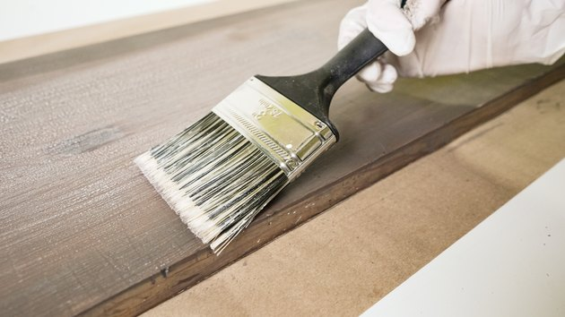 Applying whitewash for faux weathered wood finish.