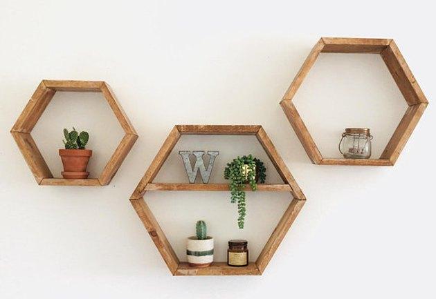 Three hexagonal wooden shelves in various sizes