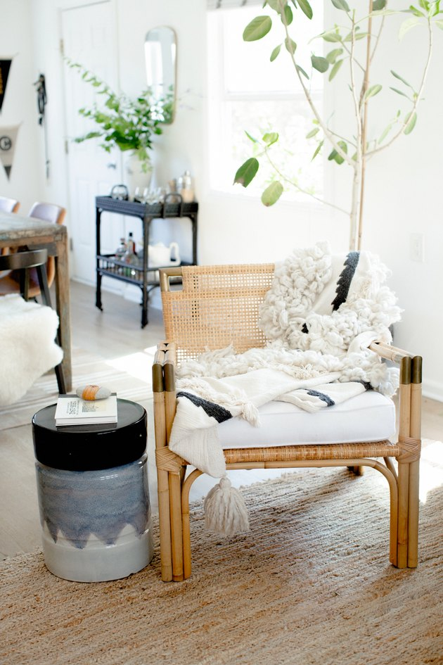 Corner of living room with textiles and rattan.