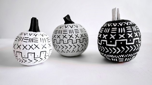 three small pumpkins painted in a black-and-white mud cloth pattern
