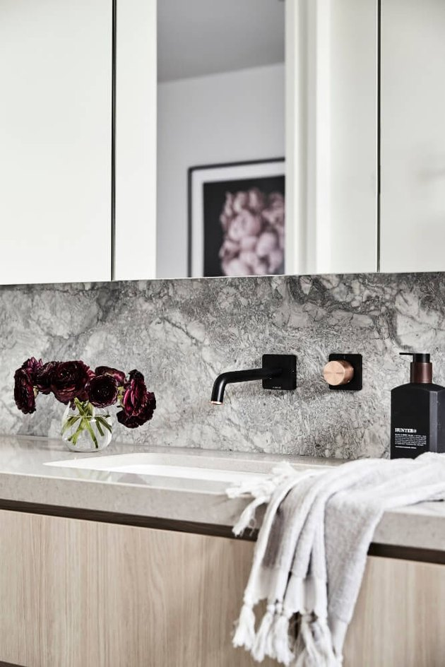 undermount bathroom sink with marble backsplash and light wood vanity