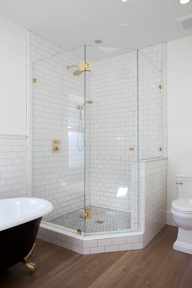 white bathroom with corner shower with glass enclosure