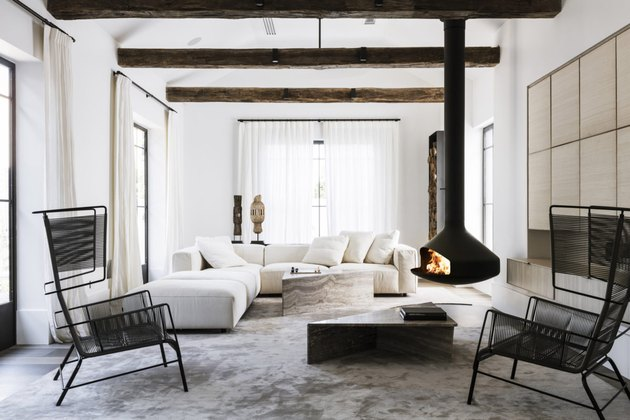 Scandinavian inspired living room with exposed ceiling beams and hanging fireplace