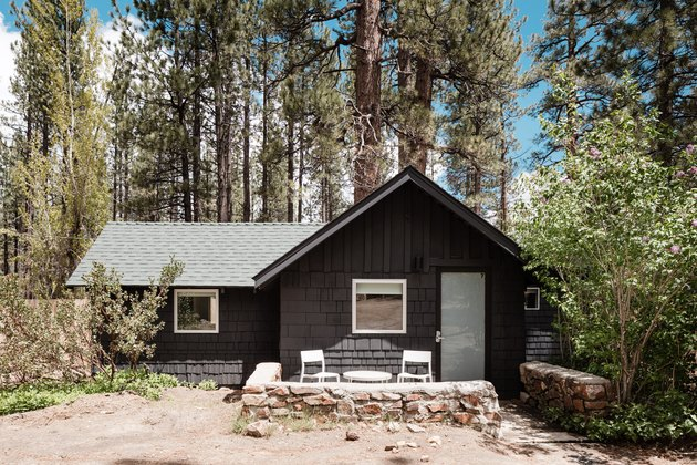 A one-story brown cabin with several trees surrounding it