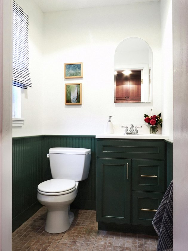 bathroom with green vanity cabinet and wainscot